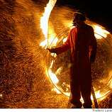 "A performer spins a fire rope in front of the ""Wheel of Thwarted Ambition"" that also throws off sparks at Burning Man 2008."