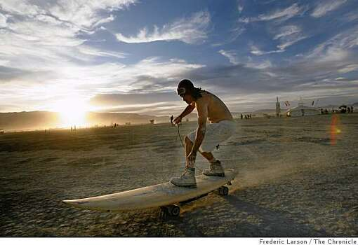 Donald Cassel of Venice, Calif. gets around the playa at Burning Man on a motorized surfboard. Photo: Frederic Larson, The Chronicle