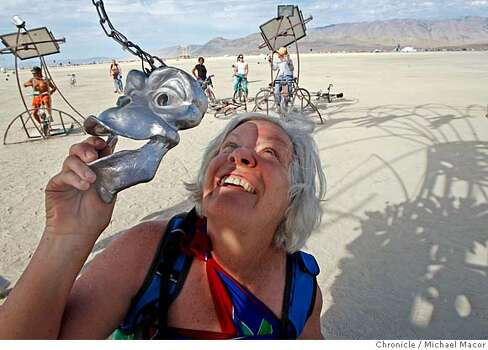 Mary Kirk of Boulder, Co., checks out the Swirling Vortex artpiece on the Playa. Ten bicycles are pedaled to produce enough energy to spin a carousel of monkeys. The monkey mask has a special glass to see a strobe effect hitting the monkeys. Burning Man 2007.  Photo: Michael Macor