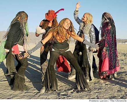 Autumn Champion and Seychell Gomolicke (center left to right)  with other revelers from Mendocino County, Cailf., dance to the rave music that plays all night to past sunrise during the Burning Man festival at Black Rock NV, on August 29, 2008. Photo: Frederic Larson, The Chronicle