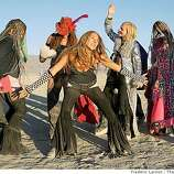 Autumn Champion and Seychell Gomolicke (center left to right)  with other revelers from Mendocino County, Cailf., dance to the rave music that plays all night to past sunrise during the Burning Man festival at Black Rock NV, on August 29, 2008.