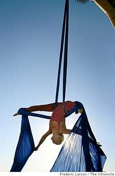 "Jennifer Hill a aerial artist from Seattle hangs off the ""Basura Sagrada"" shrine at sunrise during Burning Man 2008, at Black Rock NV, on August 28, 2008. Photo: Frederic Larson, The Chronicle"