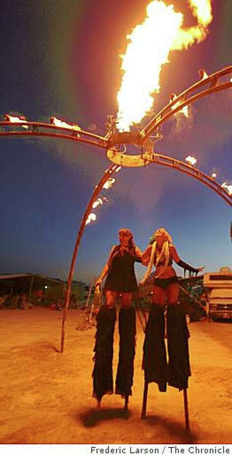 "Freda Rowley (left) and Polly Bates of Boonville, Calif., on stilts walk under a flaming exhibit called ""Voodo Shooting Gallery"" at the Burning Man 2008, at Black Rock NV, on August 26, 2008. Photo: Frederic Larson, The Chronicle"