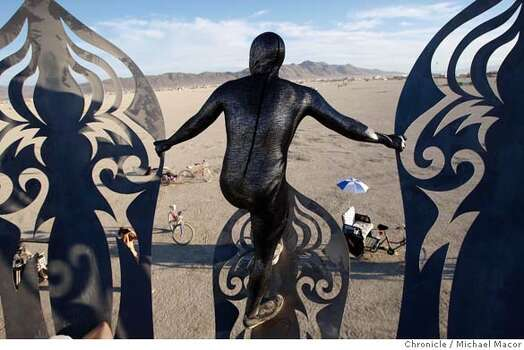 "Judah Earl of Phoenix, Az. peers across the Playa from the metal sculpture ""Guardian of Eden,"" by Kate Raudenbush, rising above the desert floor in 2007.  Photo: Michael Macor"