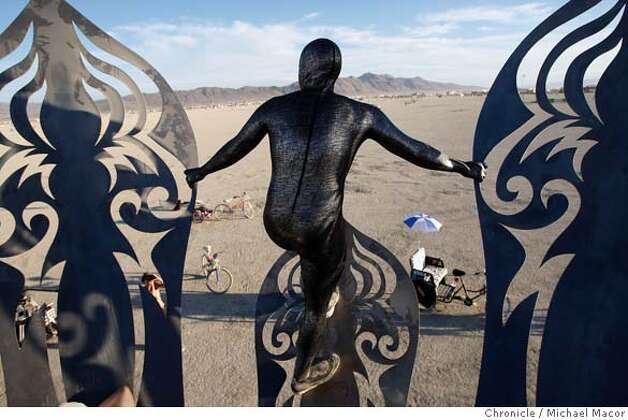 "Judah Earl of Phoenix, Az. peers across the Playa from the metal sculpture,""Guardian of Eden"" by Kate Raudenbush, rising above the desert floor. Burning Man 2007 gets up and running, officially starting yesterday. Photographed in, Black Rock City, Nv, on 8/28/07. Photo by: Michael Macor/ The Chronicle Photo: Michael Macor"