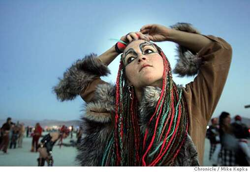 Erin Shredder, of Humbolt, CA makes a final adjustment to her hair before her fire dance performance on burn night at Burning Man 2005.  Photo: Mike Kepka