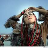Erin Shredder, of Humbolt, CA makes a final adjustment to her hair before her fire dance performance on burn night at Burning Man 2005.