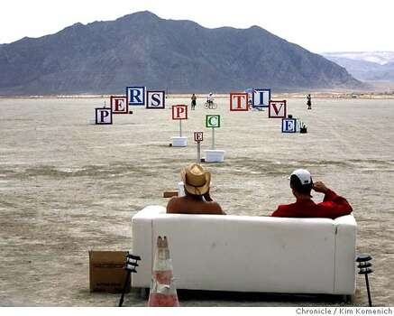 "Burning Man festivalgoers sit on a couch to experience the alignment of blocks spelling the word ""perspective"" at Trey Watkins' ""Perspective"" installation.  Photo: Kim Komenich"