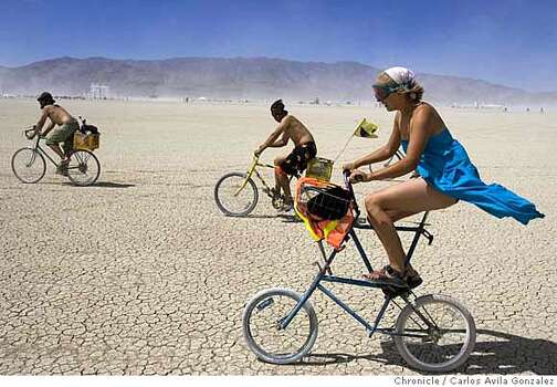 Kelly Peach of Bellingham, Wa., fights the wind as she rides her bike on the Playa during the Burning Man Festival on Tuesday, August 29, 2006.  Photo: Carlos Avila Gonzalez