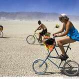 Kelly Peach of Bellingham, Wa., fights the wind as she rides her bike on the Playa during the Burning Man Festival on Tuesday, August 29, 2006.