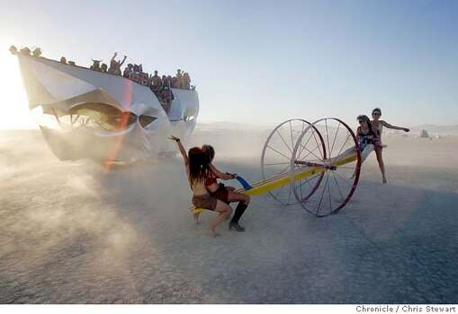An art vehicle passes by four women as they power a giant mobile teeter-totter across the Playa at sunset during Burning Man 2005.  Photo: Chris Stewart