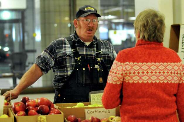 Joe O'Brien of Healthway Farms in Highland, center, assists fellow farmer Melanie Mason of Longlesson Farm in Buskirk during the indoor farmers' market on Wednesday, Feb. 8, 2012, at the Empire State Plaza Concourse in Albany, N.Y. (Cindy Schultz / Times Union) Photo: Cindy Schultz / 00016368A