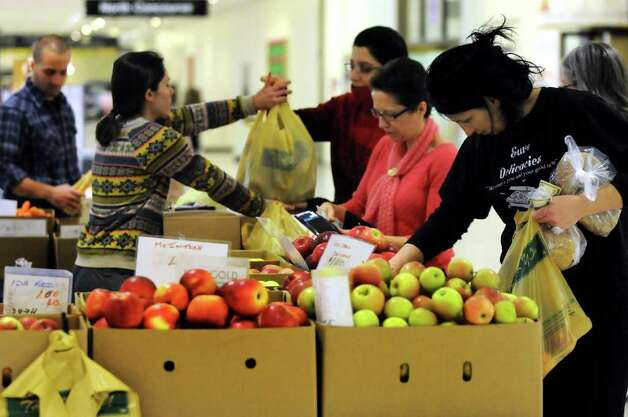 Customers shop for produce at the Healthway Farms stand during the indoor farmers' market on Wednesday, Feb. 8, 2012, at the Empire State Plaza Concourse in Albany, N.Y. (Cindy Schultz / Times Union) Photo: Cindy Schultz / 00016368A