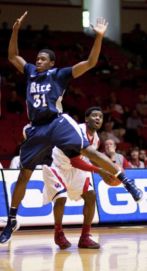 Rice University guard Dylan Ennis (31) flies by University of Houston guard J.J. Thompson (3) on a pump fake during the first half of a NCAA basketball game, Wednesday, Feb. 8, 2012, in Hofheinz Pavillionin Houston. Photo: Nick De La Torre, Houston Chronicle / © 2012  Houston Chronicle