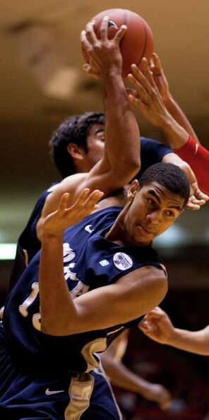 Rice University guard Julian DeBose (15) gets caught up in an array of arms, including his teammates