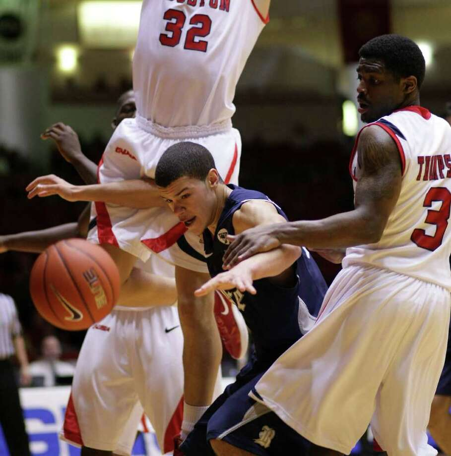 Rice University forward Jarelle Reischel (12) looses control of the ball as University of Houston forward Kirk Van Slyke (32) and the Cougars fill the paint during the second half of a NCAA basketball game, Wednesday, Feb. 8, 2012, in Hofheinz Pavillion in Houston. Rice University won 79-71. Photo: Nick De La Torre, Houston Chronicle / © 2012  Houston Chronicle