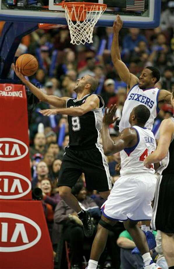 San Antonio Spurs' Tony Parker (9) goes up for a basket as Philadelphia 76ers' Andre Iguodala, top right, and Elton Brand (42) defend in the second half of an NBA basketball game on Wednesday, Feb., 8, 2012, in Philadelphia. The Spurs won 100-90. (AP Photo/H. Rumph Jr ) Photo: H. Rumph Jr, Associated Press / FR61717 AP
