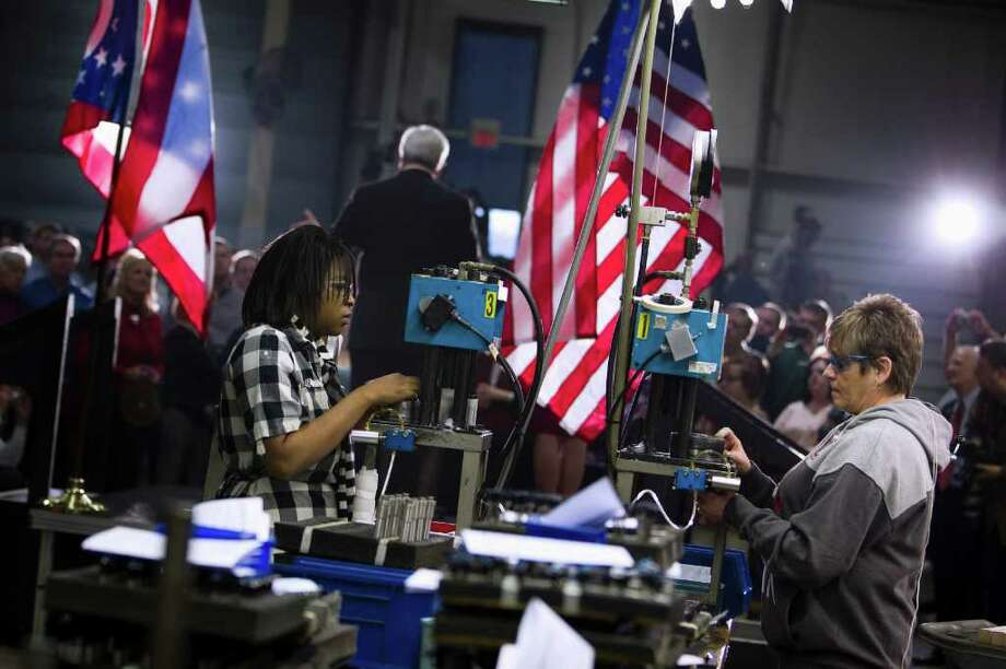 Employees of Jergens, Inc., continue to work on the assembly line as Republican presidential candidate, former House Speaker Newt Gingrich speaks during a campaign stop, Wednesday, Feb. 8, 2012, in Cleveland, Ohio. Photo: Evan Vucci, Associated Press / AP