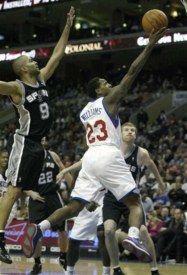 San Antonio Spurs' Tony Parker (9) defends as Philadelphia 76ers' Lou Williams (23) goes up for a shot in the second half of an  NBA basketball game on Wednesday, Feb., 8, 2012, in Philadelphia. The Spurs won 100-90. (AP Photo/H. Rumph Jr ) Photo: H. Rumph Jr, Associated Press / FR61717 AP