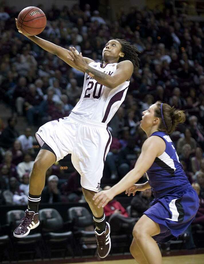 Texas A&M's Tyra White (20) scores past Kansas State's Brittany Chambers during the first half of an NCAA college basketball game at Reed Arena in College Station, Texas, Wednesday, Feb. 8, 2012. Photo: AP