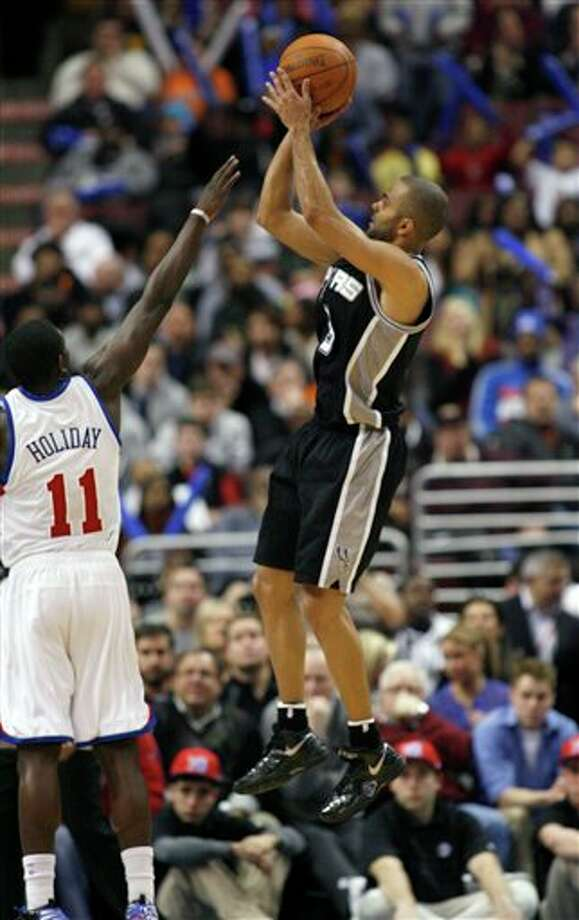 San Antonio Spurs' Tony Parker, right, goes up for shot as Philadelphia 76ers' Jrue Holiday (11) defends in the second half of an NBA basketball game on Wednesday, Feb., 8, 2012, in Philadelphia. The Spurs won 100-90. (AP Photo/H. Rumph Jr ) Photo: H. Rumph Jr, Associated Press / FR61717 AP
