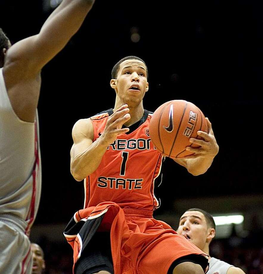 Oregon State guard Jared Cunningham (1) flies in for a layup attempt after getting between Washington State forward forward DeAngelo Casto, left, and guard Klay Thompson, right, during the first half of an NCAA college basketball game Thursday, Jan. 6, 2011, in Pullman, Wash. Photo: Dean Hare, AP