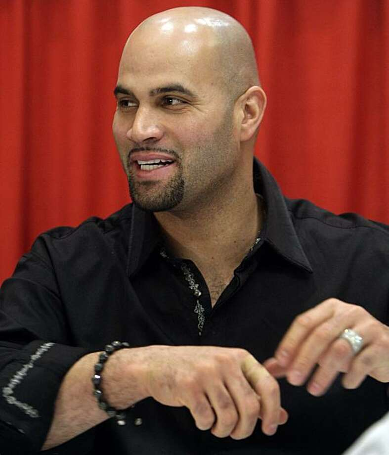 St. Louis Cardinals first baseman Albert Pujols adjusts his arms as he signs autographs for fans at the Cardinals' annual Winter Warm-Up event Monday, Jan. 18, 2010, in St. Louis. Photo: Jeff Roberson, AP