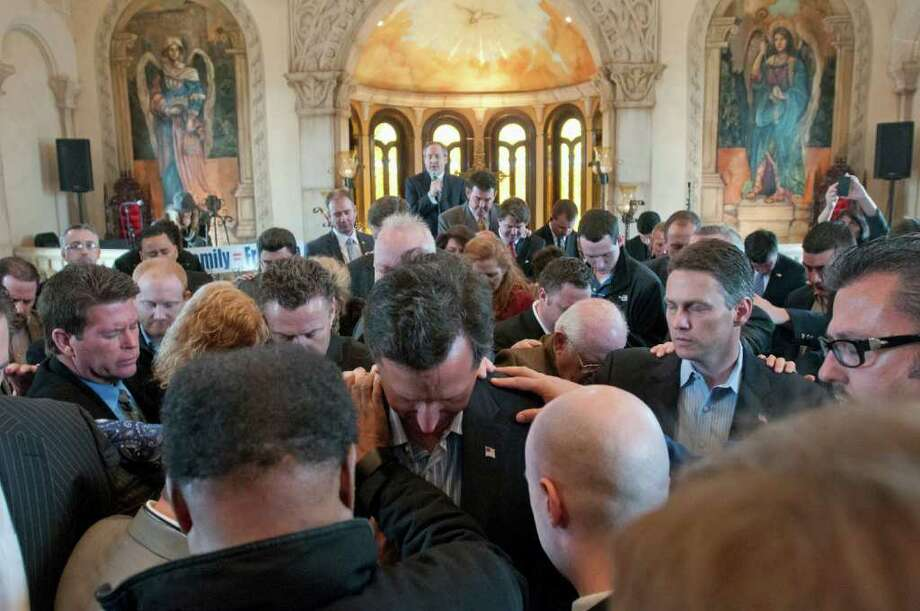 GOP presidential contender Rick Santorum, formerly a U.S. senator from Pennsylvania, is prayed over after speaking at Bella Donna Chapel in McKinney, Texas. Photo: Rex C. Curry / FR41626AP