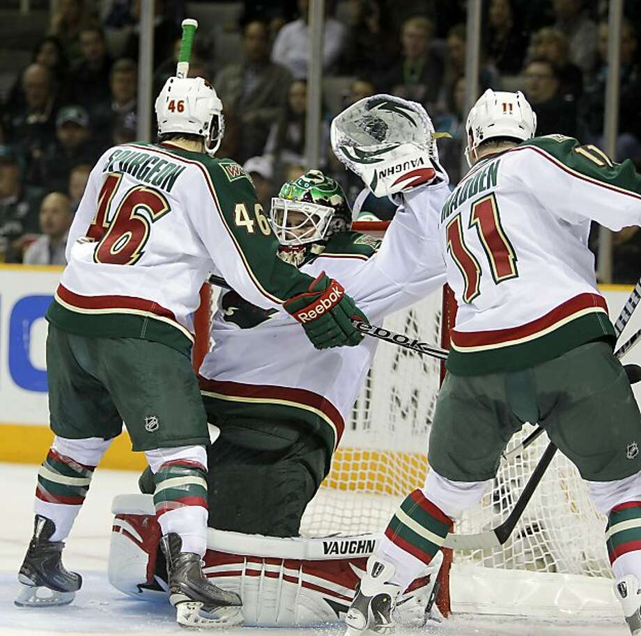 Minnesota Wild goalie Niklas Backstrom, center, attempts to stop the puck accidentally hit in for a goal by a teammate, as Madden (11) and Jared Spurgeon (46) stand in front of the goal during the second period of an NHL hockey game against the San Jose Sharks Thursday, March 17, 2011, in San Jose, Calif. Sharks' Logan Couture was credited with the goal. Photo: AP