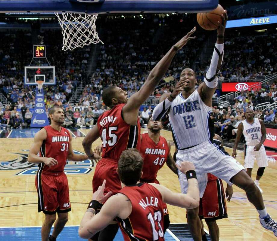 Orlando's Dwight Howard (12) takes a shot over Miami's Dexter Pittman (45) on Wednesday in Orlando. Photo: John Raoux / AP