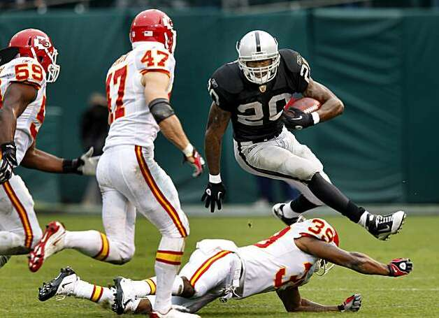 Darren McFadden goes up in the air to get by some Chiefs defenders in the second half Sunday. Photo: Brant Ward, The Chronicle