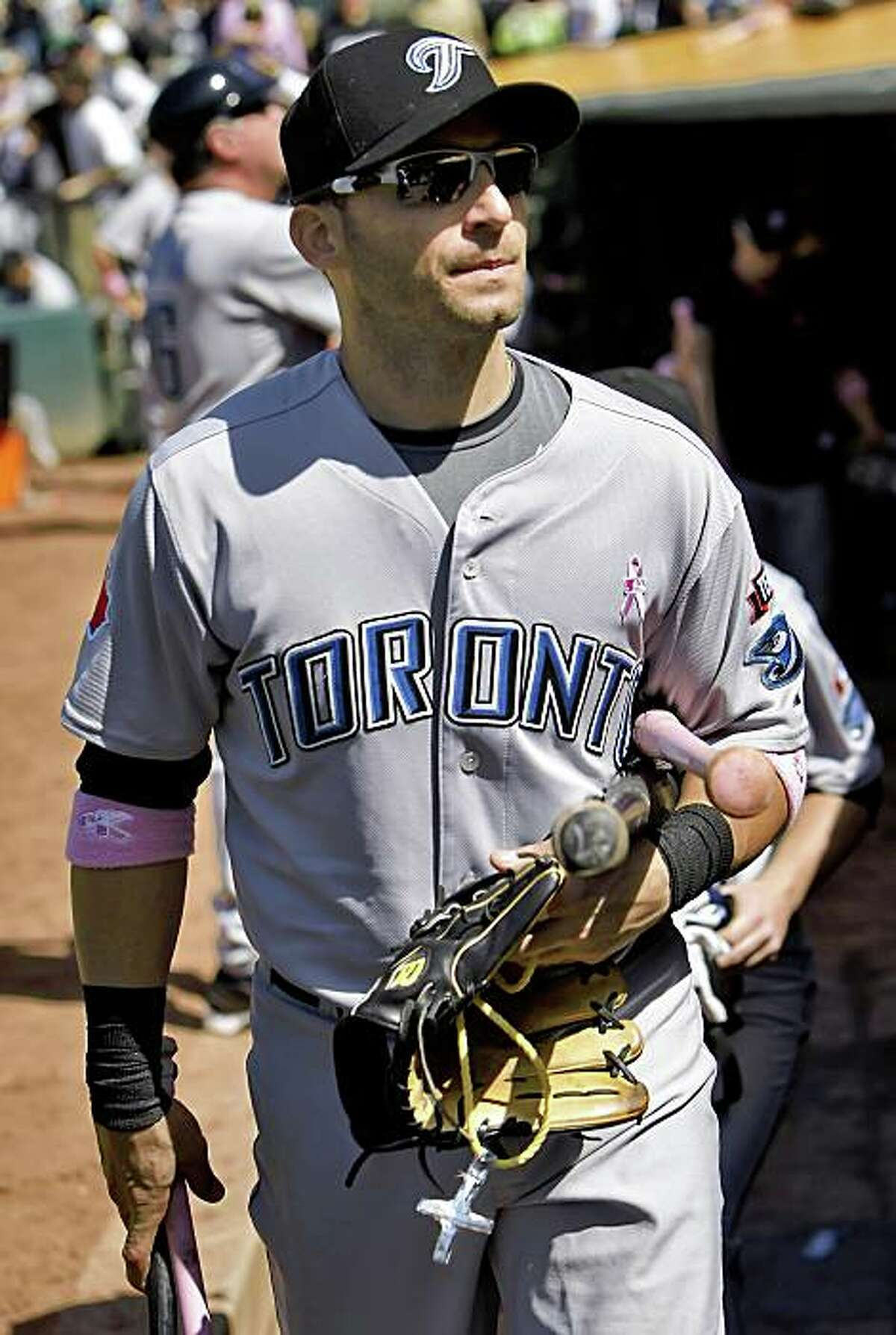 Former Oakland Athletic, Marco Scutaro, walks off the field after the Toronto Blue Jays defeated the A's carrying his equipment and a little crucifix fashioned from plastic rope and tin foil. The crucifix was given to Scutaro by the grounds crew at the Coliseum after Scutaro lost his gold crucifix during a game Friday night. The Oakland Athletics played the Toronto Blue Jays at the Oakland-Alameda County Coliseum in Oakland, Calif., on Sunday, May 10, 2009. The Blue Jays won the game 5-0.