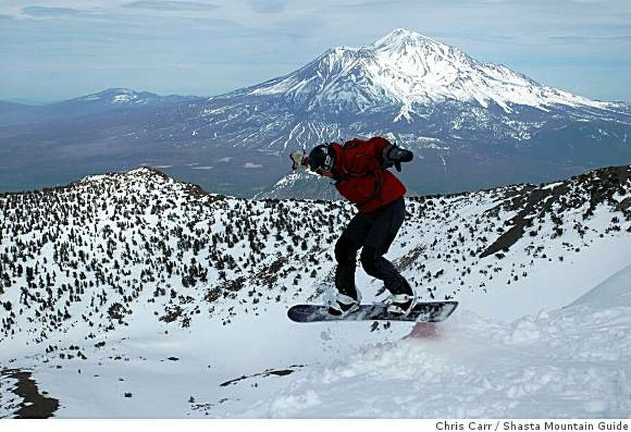 Chet Kyle snowboards over a jump at the summit of 9,025-foot Mount Eddy with 14,162-foot Mount Shasta looming to the east. Photo: Chris Carr, Shasta Mountain Guide