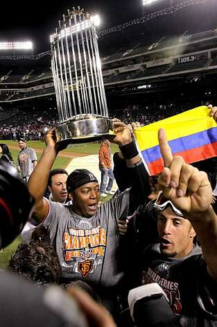 Giants Edgar Renteria, parades around the championship trophy along with teammate Andres Torres,  following San Francisco's win of the 2010 World Series over the Texas Rangers on Monday Nov. 1, 2010 in Arlington, Tx., with a score of 3-1. Photo: Michael Macor, San Francisco Chronicle