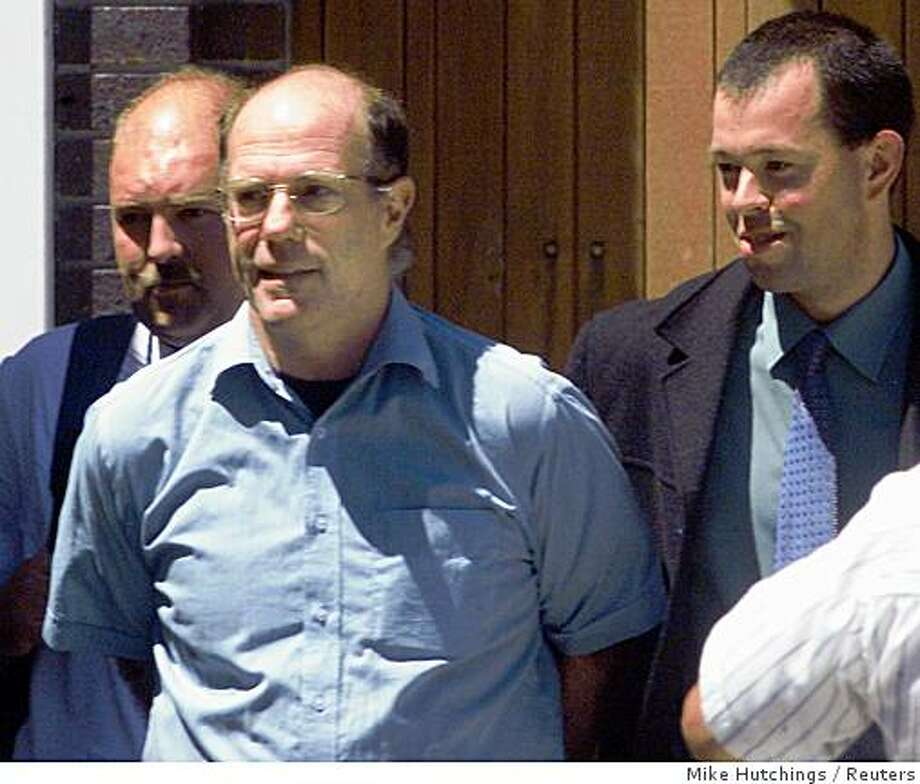 James Kilgore (C), the last fugitive member of the Symbionese Liberation Army (SLA), leaves a Cape Town magistrates court after an extradition hearing, November 11, 2002. Kilgore, arrested in South Africa November 8 after 27 years on the run, could be extradited soon to the United States since objections he may be executed are ill-founded, a U.S. embassy spokesman said. REUTERS/Mike Hutchings Photo: Mike Hutchings, Reuters