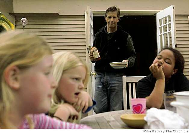 Jack Macy serves a spaghetti lunch in his back yard to eight-year-olds Caroline Hall (from left) Lydia Macy (his daughter) and Kiki Valenzuela, all second graders at Malcolm X Elementary on Tuesday April 28, 2009 in Berkeley, Calif. After receiving word that the school would be closed for at least a week due Swine Flu concerns, their parents decided that they would group resources and each take a day of the week to watch the kids. On Friday its likely they will have to hire a sitter. Photo: Mike Kepka, The Chronicle