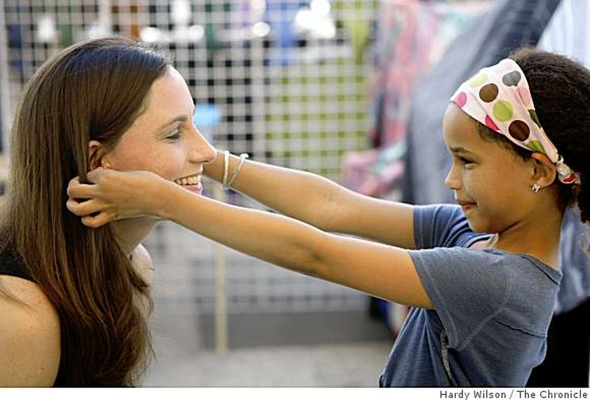 Rachel Sarah, left, and her daughter Mae Sarah, 9, pose for a picture as they play with jewelry at a stand near the ferry building in San Francisco, Calif., on Friday, April 17, 2009. An essay Rachel Sarah wrote appears in the book, 'Because I Love Her: 34 Women Writers Reflect on the Mother-Daughter Bond'.