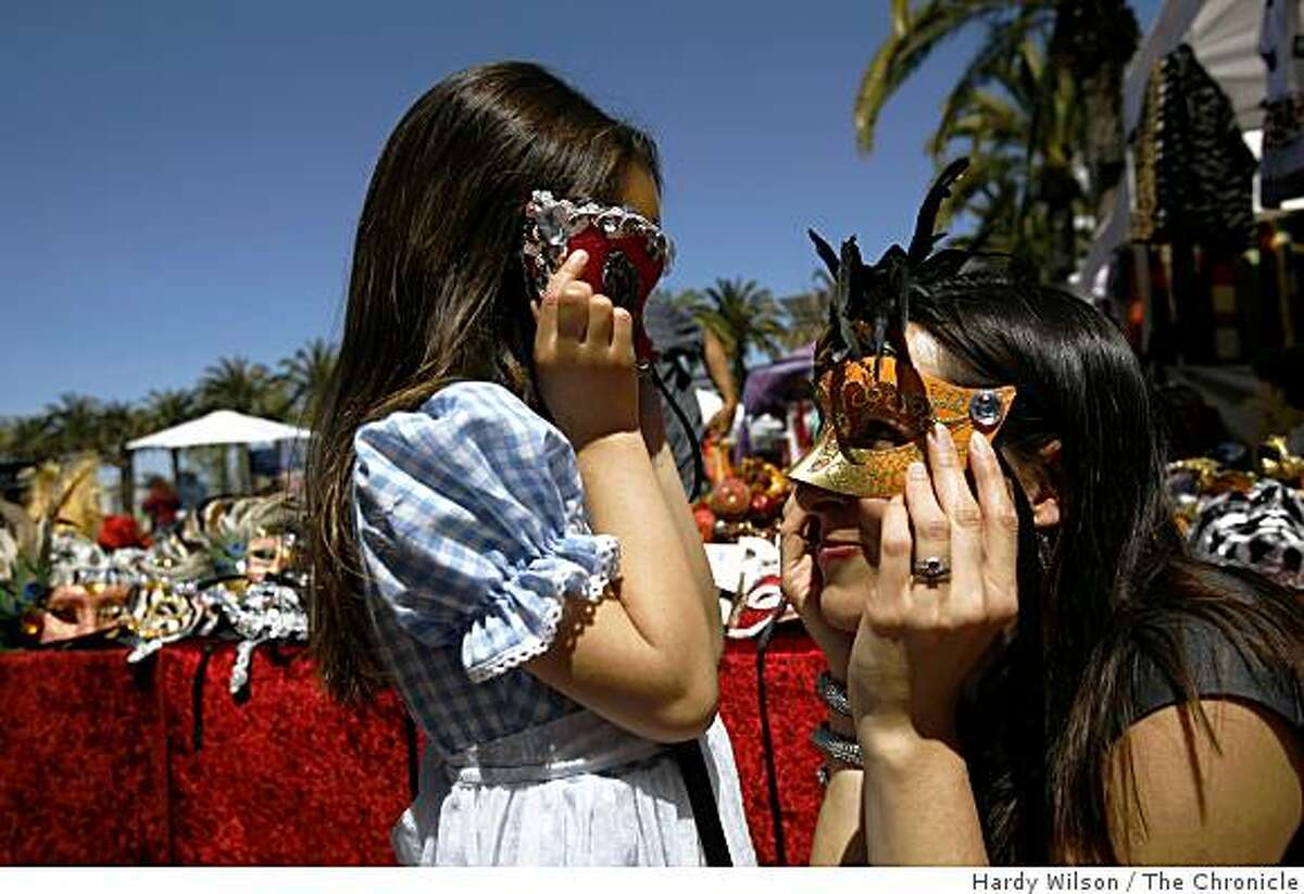 Andrea N. Richesin and her daughter Lily Warwick pose for a picture as they play with masks at a stand near the ferry building in San Francisco, Calif., on Friday, April 17, 2009. An essay RIchesin wrote appears in the book, �Because I Love Her: 34 Women Writers Reflect on the Mother-Daughter Bond�.