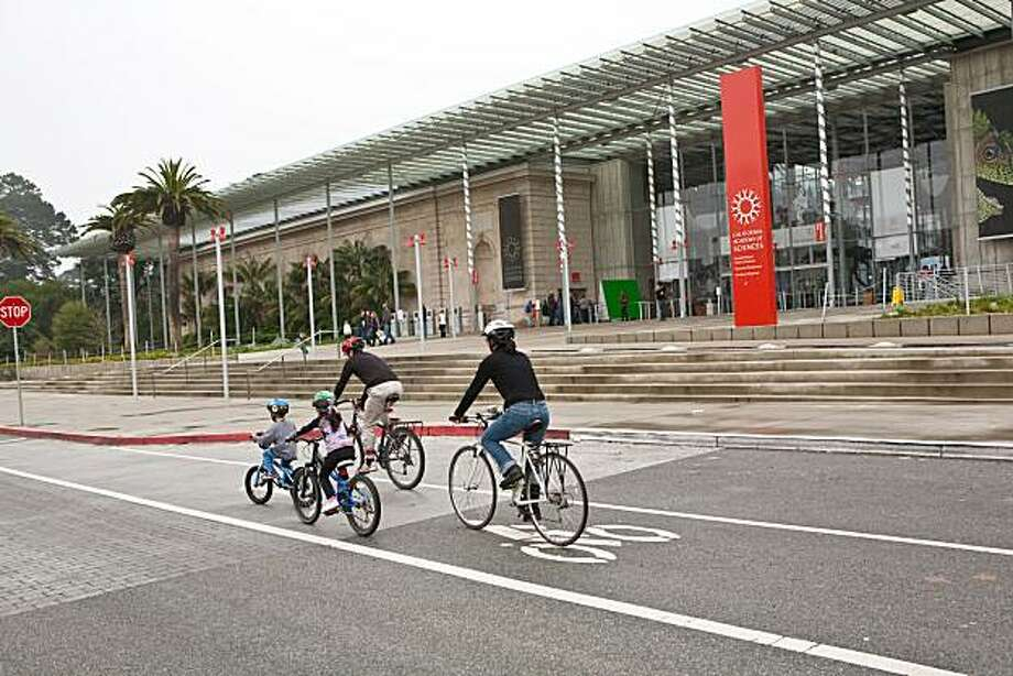 A family bikes by the California Academy of Sciences in Golden Gate Park. Photo: Tanya Dueri
