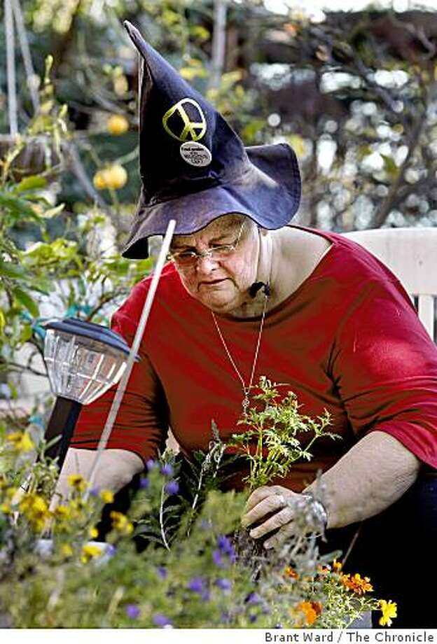 Victoria does some container planting in her backyard, which is covered with flowers. Victoria Slind-Flor, a veteran witch from Oakland, has been named the Keeper of the Light at this years 8th annual Pagan Festival in Berkeley. Photo: Brant Ward, The Chronicle