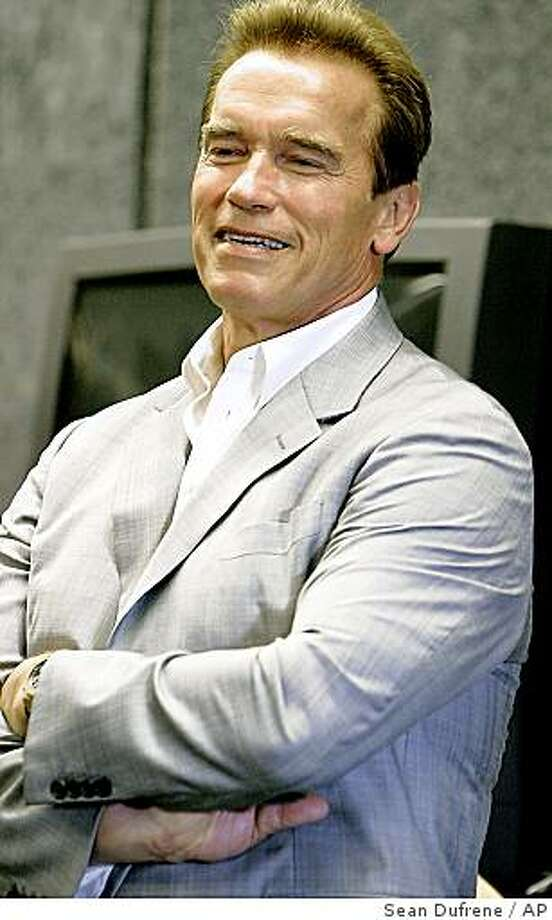 """Caption History: California Gov. Arnold Schwarzenegger listens to the Carlsbad High School band's rendition of """"Secret Agent Man"""" during a visit to the school, Friday, Aug. 11, 2006, in Carlsbad, Calif. Schwarzenegger visited the northern San Diego County school in an effort to highlight the school's arts, music and physical education program, something he says is needed in all California schools. Schwarzenegger has put aside $645 million to fund those kinds of programs Photo: Sean Dufrene, AP"""