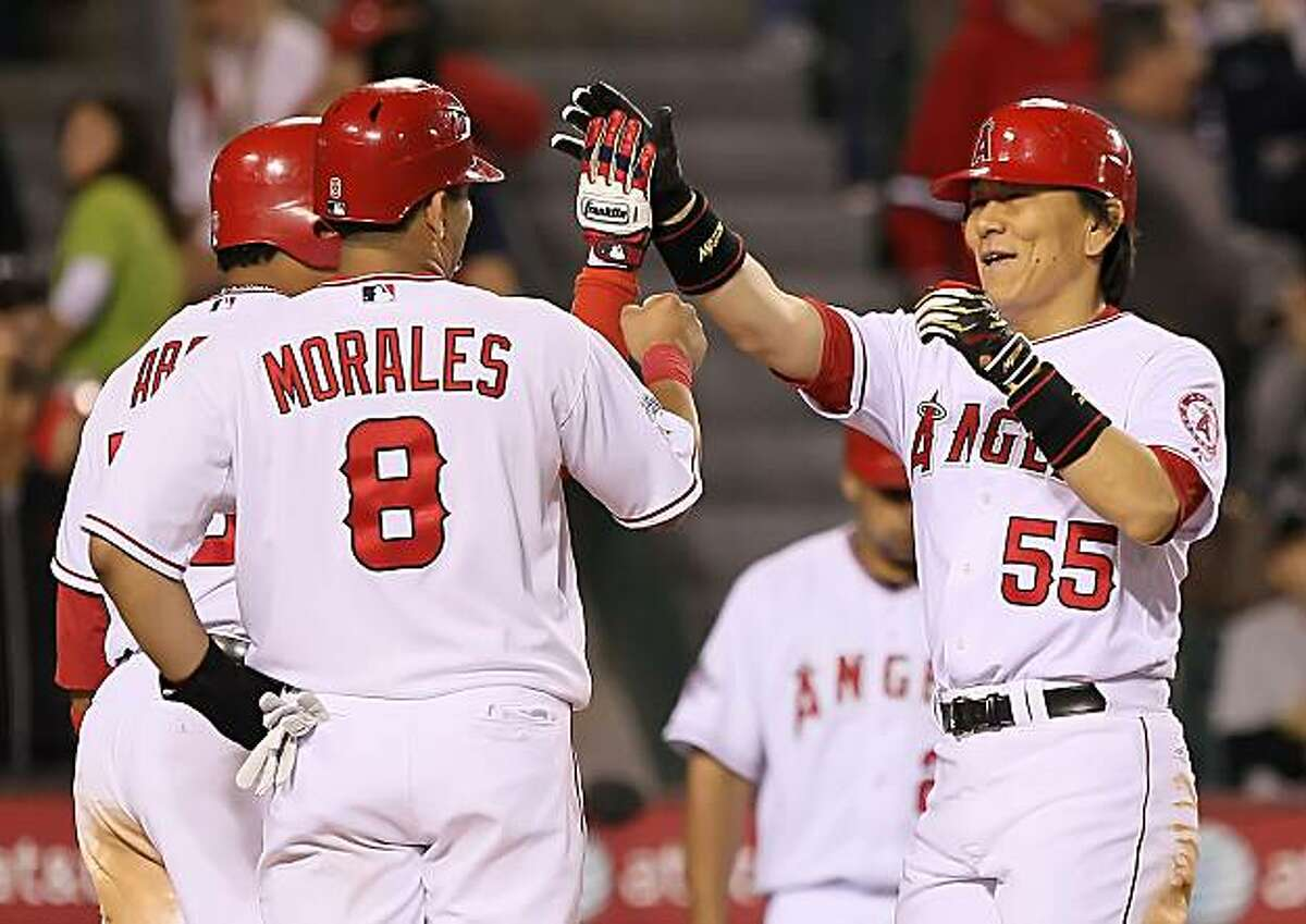 ANAHEIM, CA - MAY 14: Hideki Matsui #55 of the Los Angeles Angels of Anaheim receives high fives from teammates Bobby Abreu #53 and Kendry Morales #8 after hitting a three-run homerun against the Oakland Athletics in the sixth inning at Angel Stadium onMay 14, 2010 in Anaheim, California.