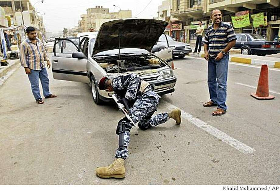 A Sunni Awakening Council member searches a vehicle at checkpoint in north Baghdad's Azamiyah neighborhood, Iraq, Sunday, May 3, 2009. Recent arrests of Awakening Council members test Iraqi government pledges to reward so-called Awakening Councils, who turned against insurgents in 2006. (AP Photo/Khalid Mohammed) Photo: Khalid Mohammed, AP