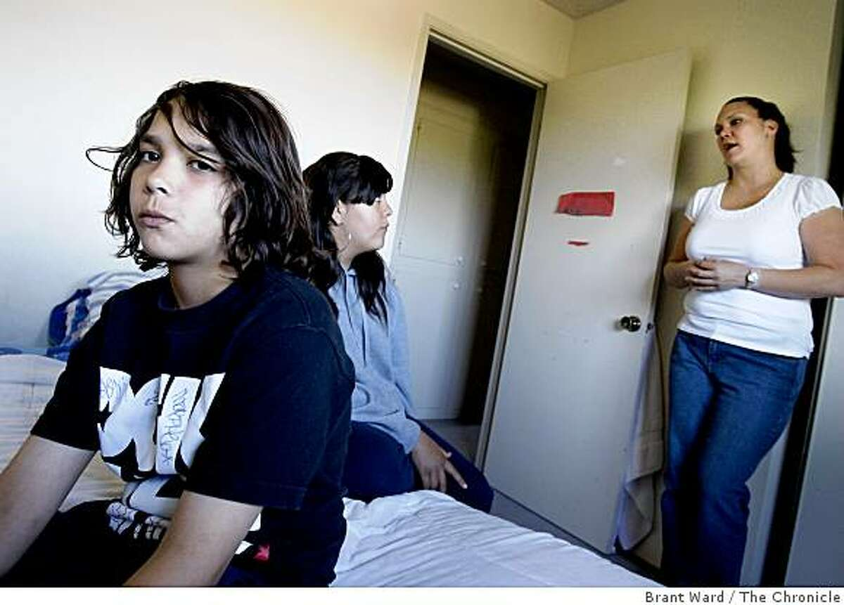Jacob Avilla (left) sits in his bedroom as his sister Roxanne (center) and mother Tammi (right) talk about plans for Thursday. As students fall victim to swine flu, schools are shutting down for a week including the Pittsburg, CA school that Jacob Avilla attends and his mother Tammi works at.