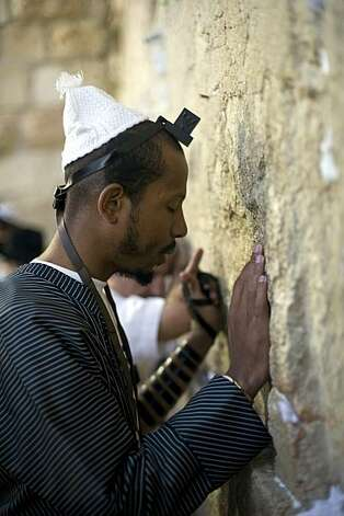 TO GO WITH AFP STORY BY SARA HUSSEIN Jewish US rapper Shyne prays at the Western Wall in Jerusalem on November 17, 2010. Scantily clad women writhing to the beat are part of the formula for almost any music video, but rapper Shyne prefers to see women more modestly attired. That might make him a minority of one in the rap world, but as a black Orthodox Jew who comfortably sports an outfit that has its basis in 19th century eastern Europe, Shyne has no qualms about being different. Photo: Lior Mizrahi, AFP/Getty Images