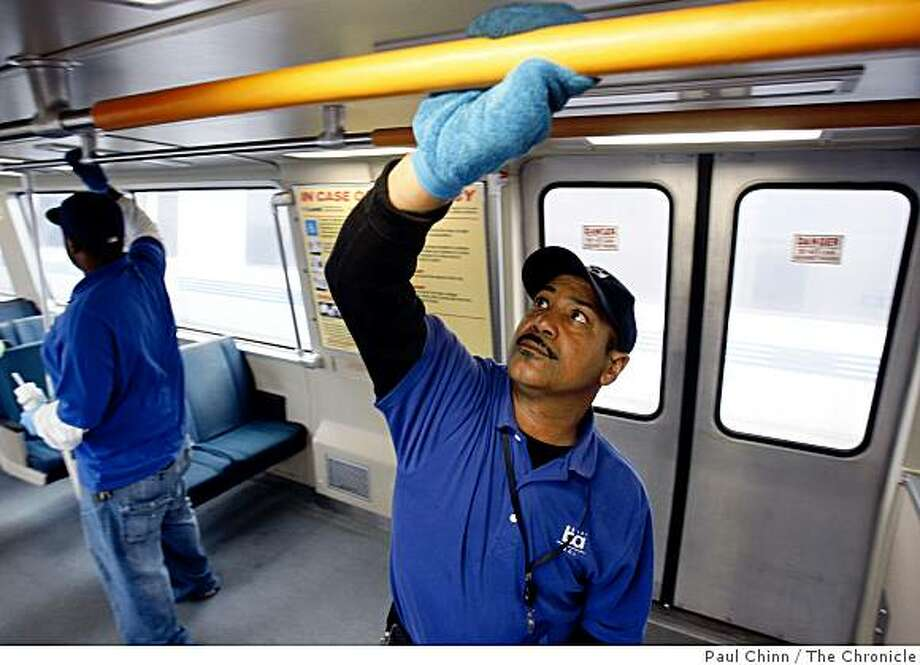 Bob Grayson (right) and Jason Branch wipes down the interior of a BART train car to minimize the risk of swine flu at the end-of-the-line at the Richmond Station. Photo: Paul Chinn, The Chronicle