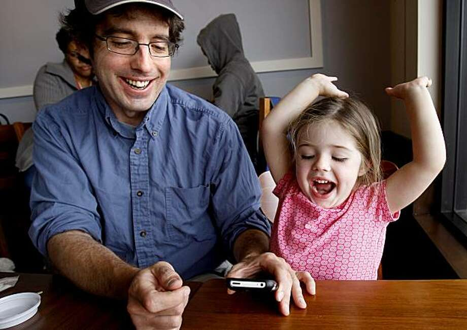Fern (right) reacts to winning an iPhone game with her father Graham. Fern Charles, a three year old from San Francisco, loves her iPhone applications that her father Graham has downloaded for her. There has been a proliferation of iPhone applications made for the toddler and preschool market. Photo: Brant Ward, The Chronicle