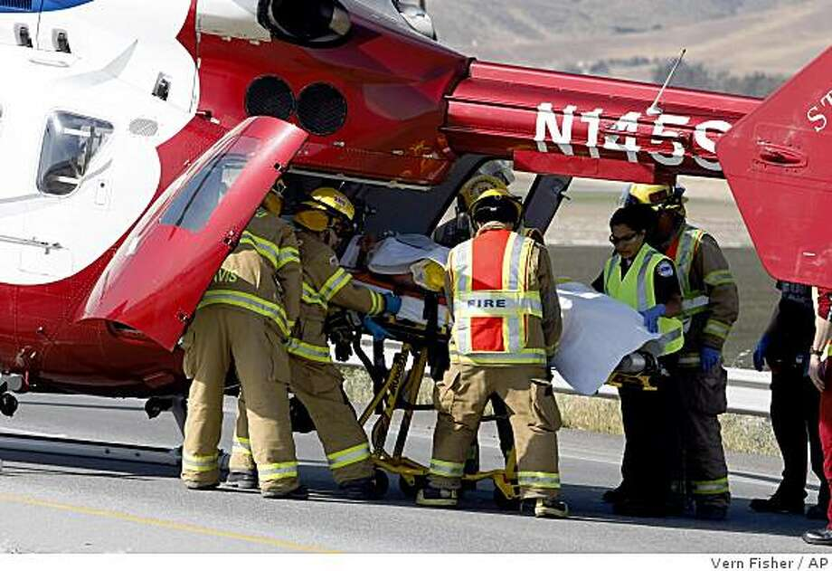 Firefighters load an injured passenger onto a helicopter Tuesday. Photo: Vern Fisher, AP