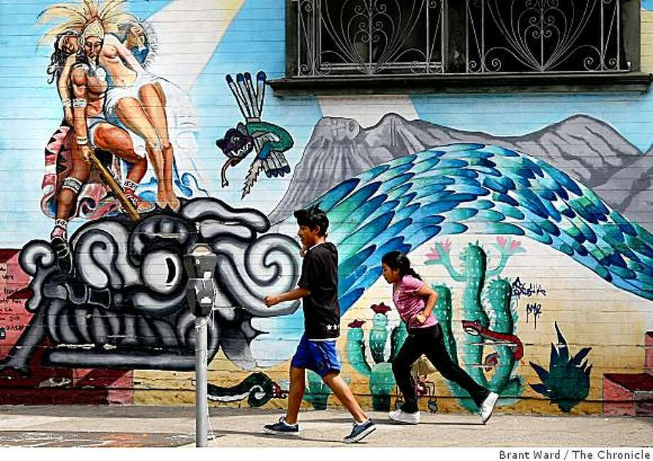 """Children run past the mural """"Leyenda Azteca"""" at the corner of 24th and Harrison Streets. This mural was restored and expanded on by students in the Precita Eyes Youth Mural Workshop. Photo: Brant Ward, The Chronicle"""