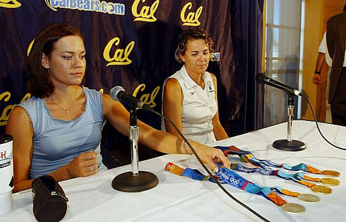 FILE - This Sept. 1, 2004, file photo shows U.S. Olympic swimmer Natalie Coughlin, left, displaying the five medals she won competing in the Athens Olympics as her coach Teri McKeever, right, sits next to her on the campus of UC Berkeley in Berkeley, Calif. USA Swimming announced Wednesday, Dec. 8, 2010, that McKeever, the longtime coach at the University of California, will lead the women's squad at the 2012 London Games.